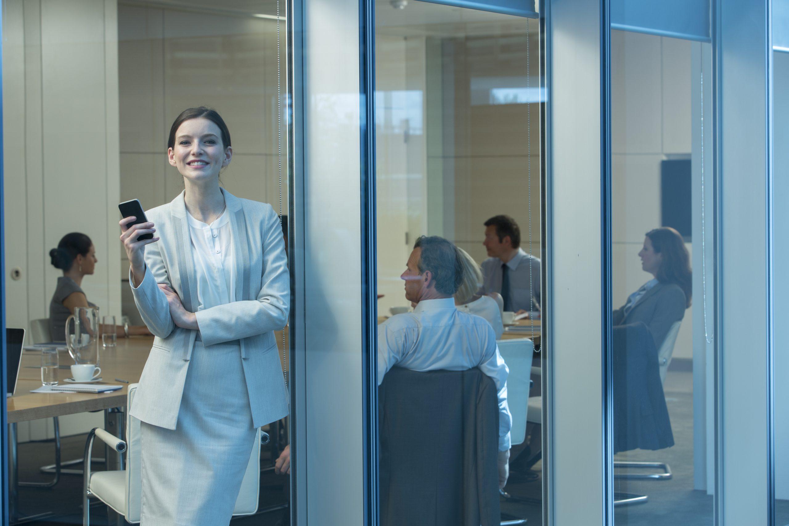 Eine geschäftlich gekleidete Frau steht lächelnd am Fenster eines Besprechungsraumes und hält ein Handy in der Hand.