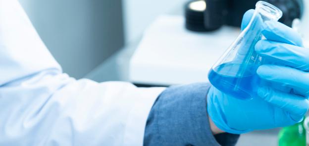 Foto einer blau behandschuhten Hand die einen Erlenmeyerkolben hält
