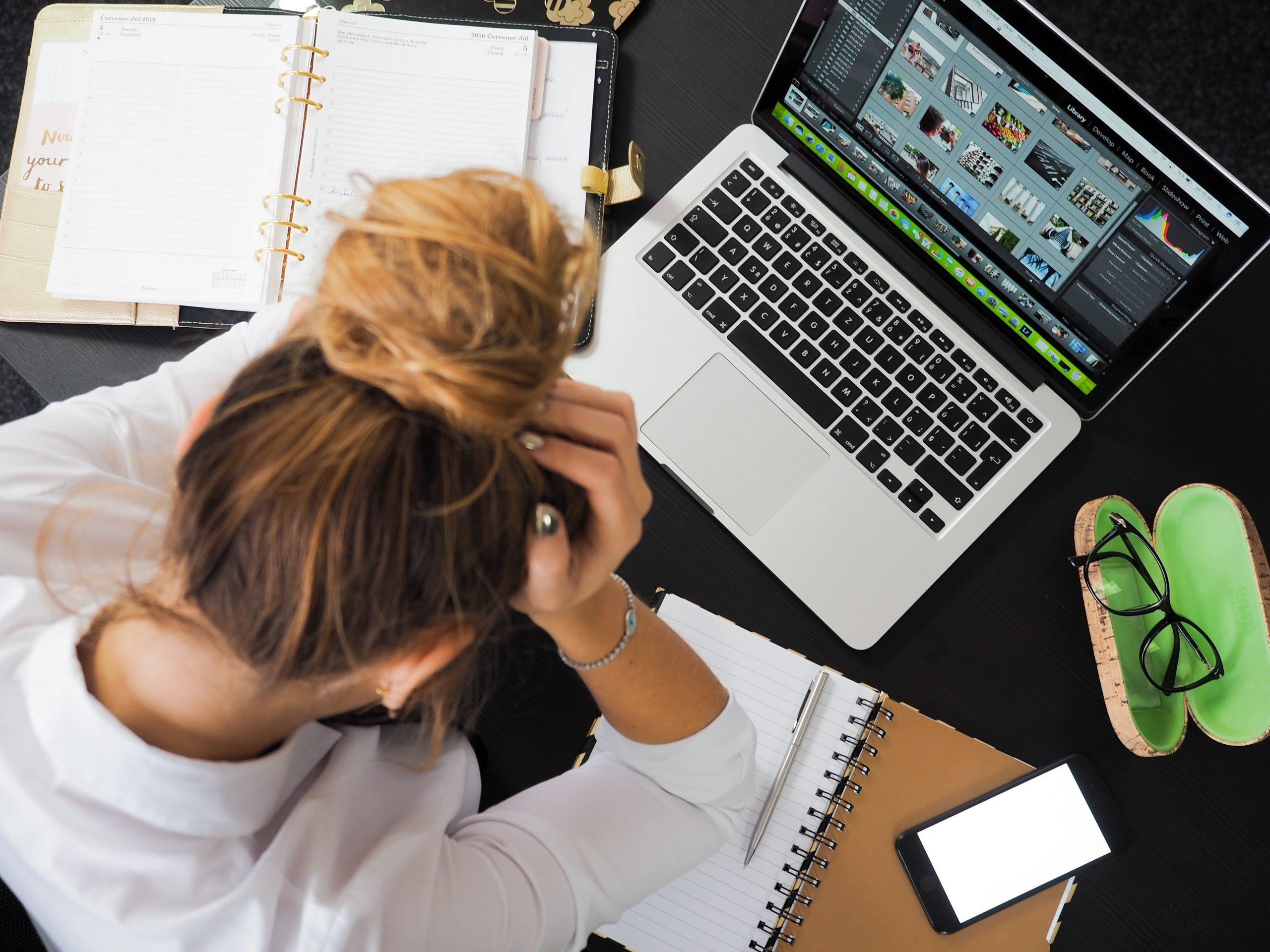 Eine Frau sitzt vor ihrem Laptop. Sie stützt in offensichtlicher Überforderung den Kopf in die Hände.