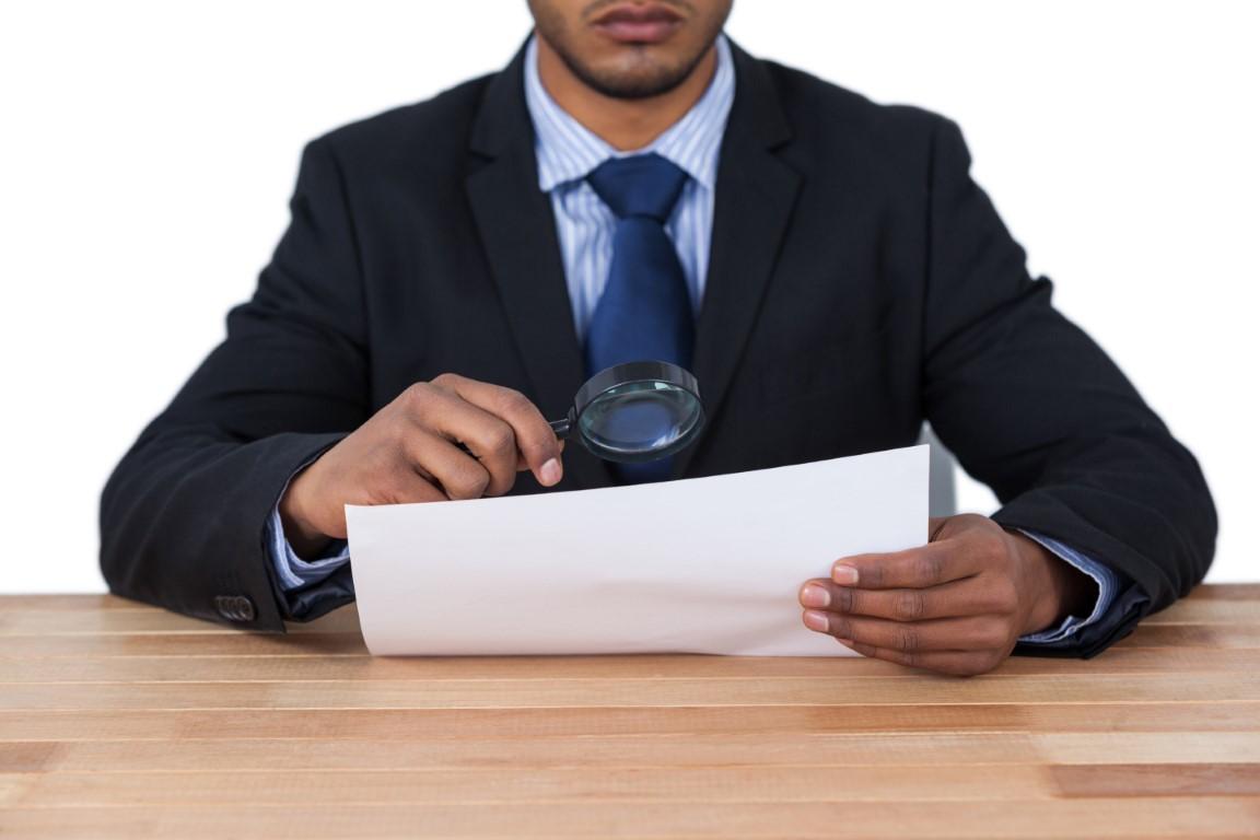 Audit - Ein Mann in einem dunklen Anzug prüft mit einer Lupe akribisch ein Dokument,