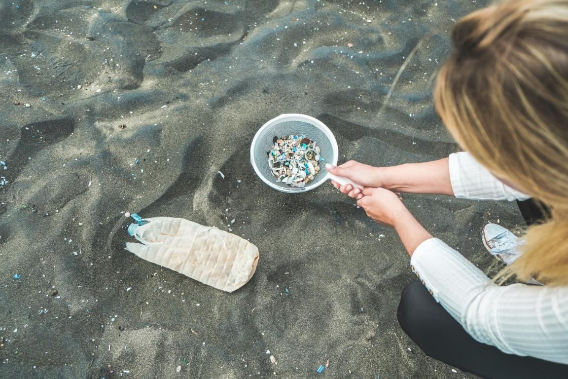 Eine junge Frau hockt am Strand und filtert mit einem Sieb Plastikpartikel aus dem Wasser.