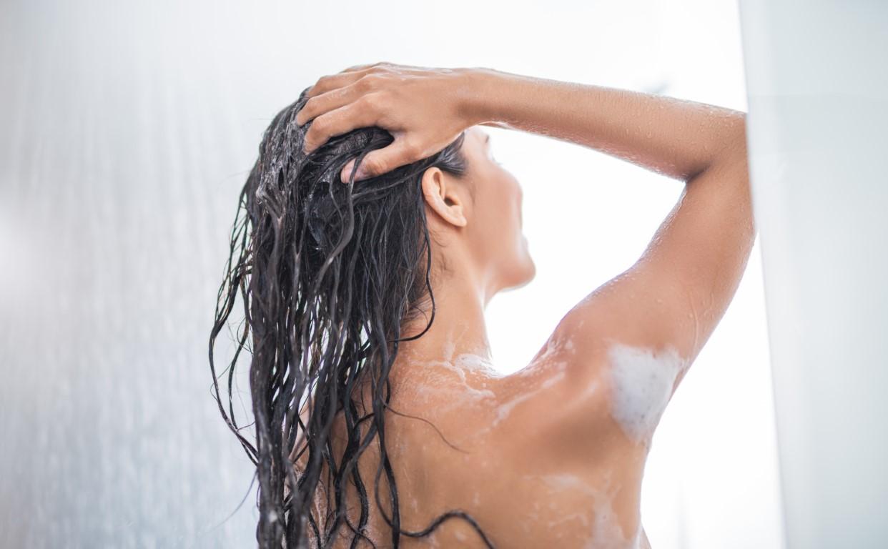Eine Frau die Shampoo benutzt während sie duscht. Sie dreht den Rücken zur Kamera.