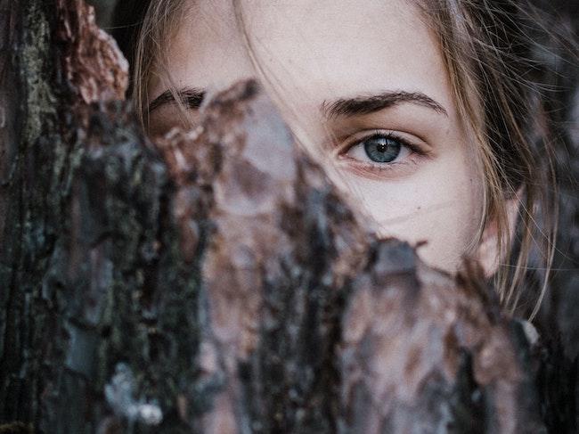 Eine Frau schaut hinter einem Stück Holz hervor direkt in die Kamera. Das Bild betont ihr Auge.
