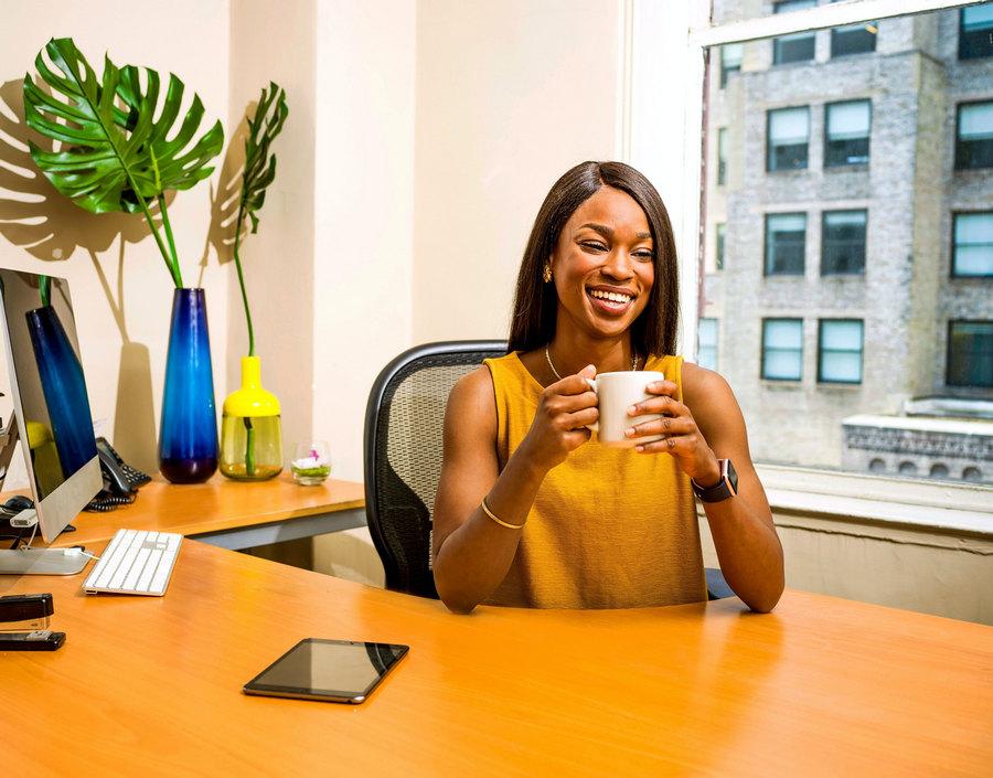 Eine Frau sitzt gut gelaunt in ihrem Büro