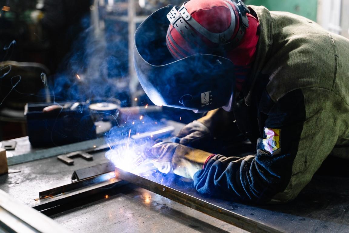 ein Schweißer/Metallbauer in persönlicher Schutzausrüstung bei der Arbeit