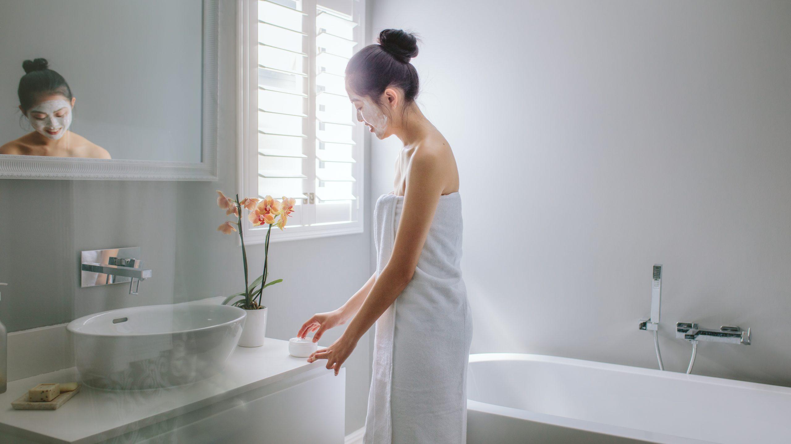 Eine junge in ein Handtuch gehüllte Frau wendet eine Gesichtscreme an