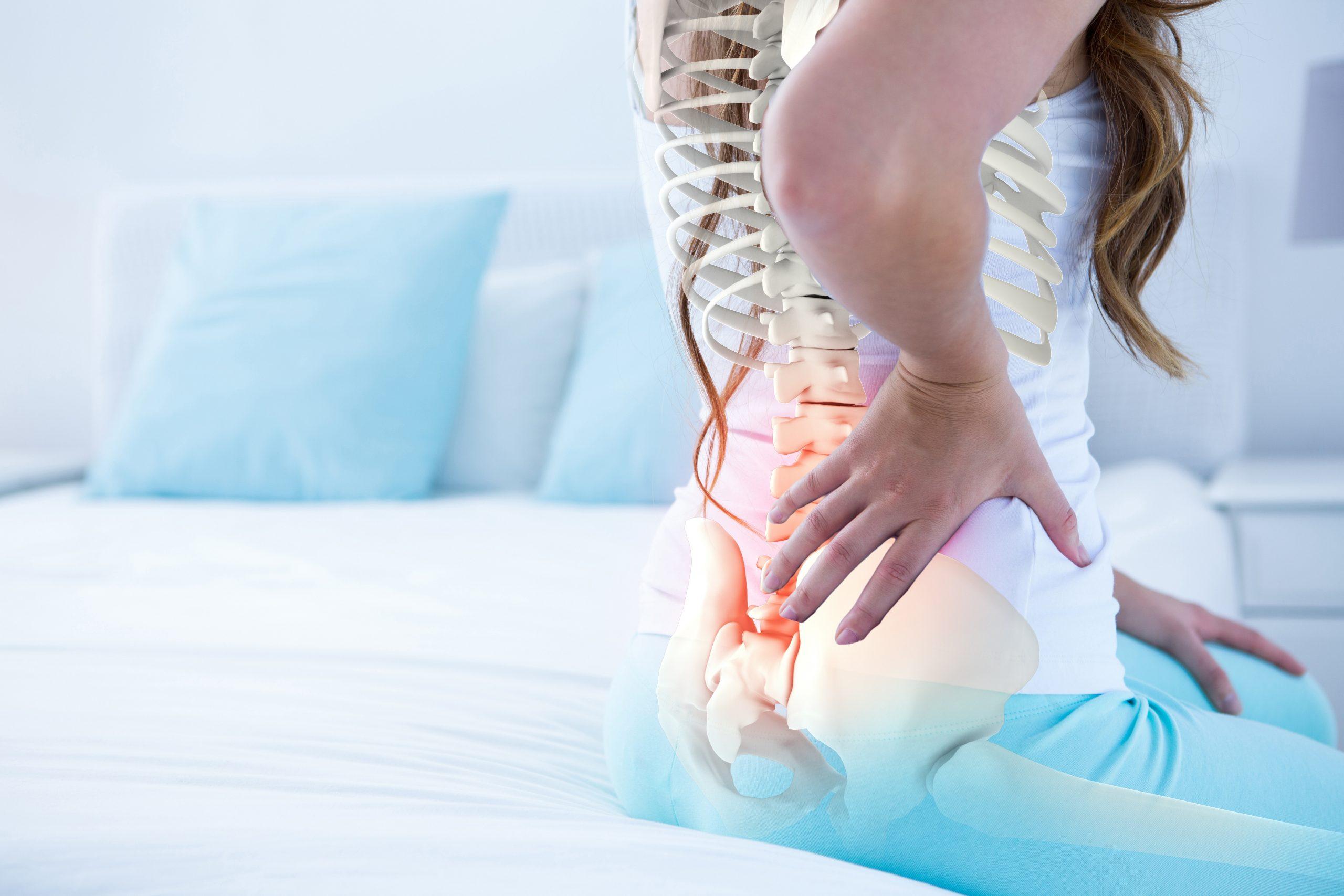 Foto einer sitzenden Frau, die offensichtlich Schmerzen im unteren RÜckenbereich hat