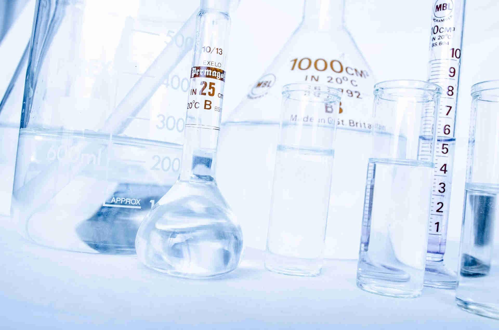 Mehrere Laborgeräte aus Glas die mit einer klaren Flüssigkeit gefüllt sind