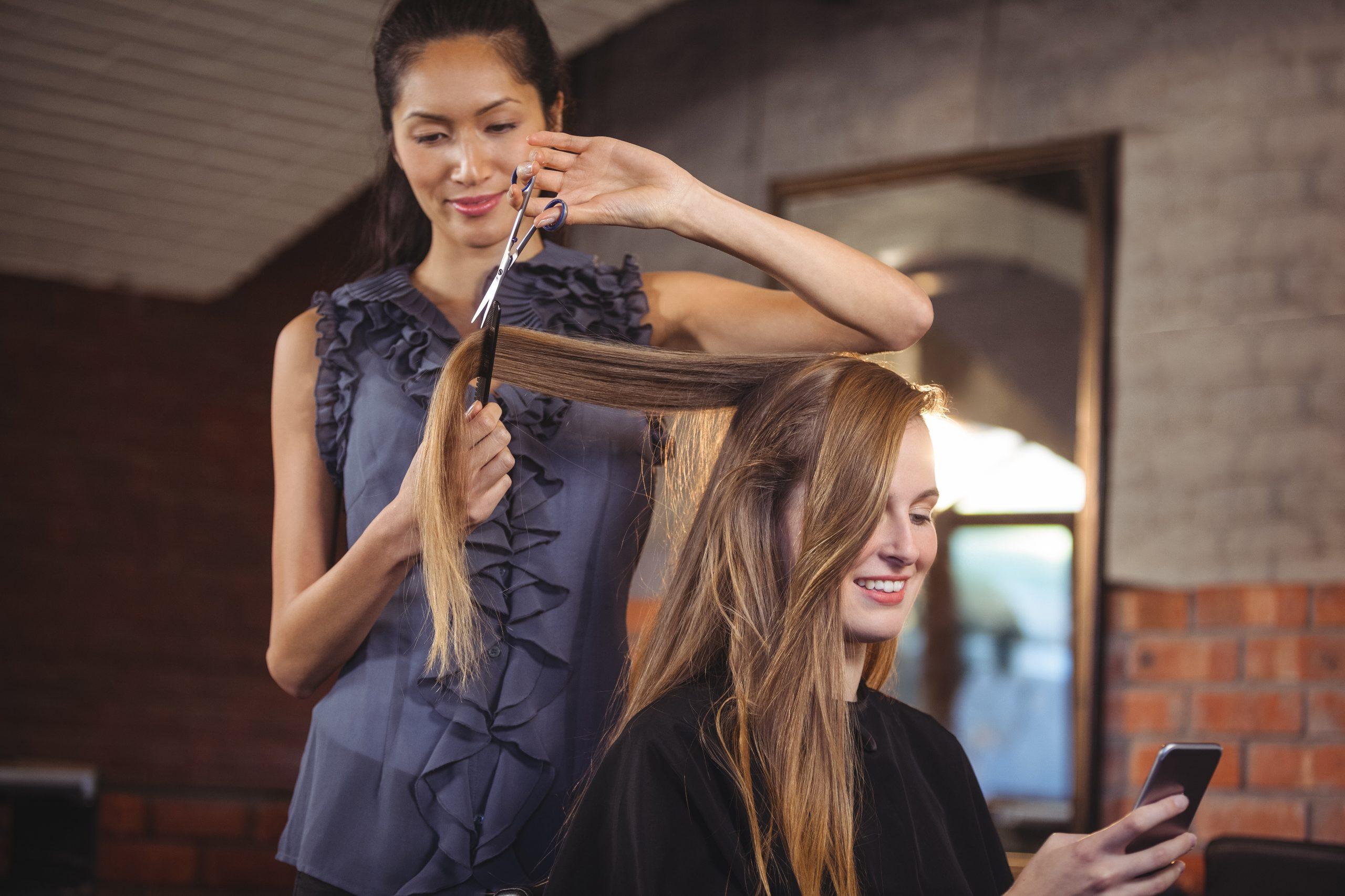 Eine Friseurin bedient eine langhaarige Kundin