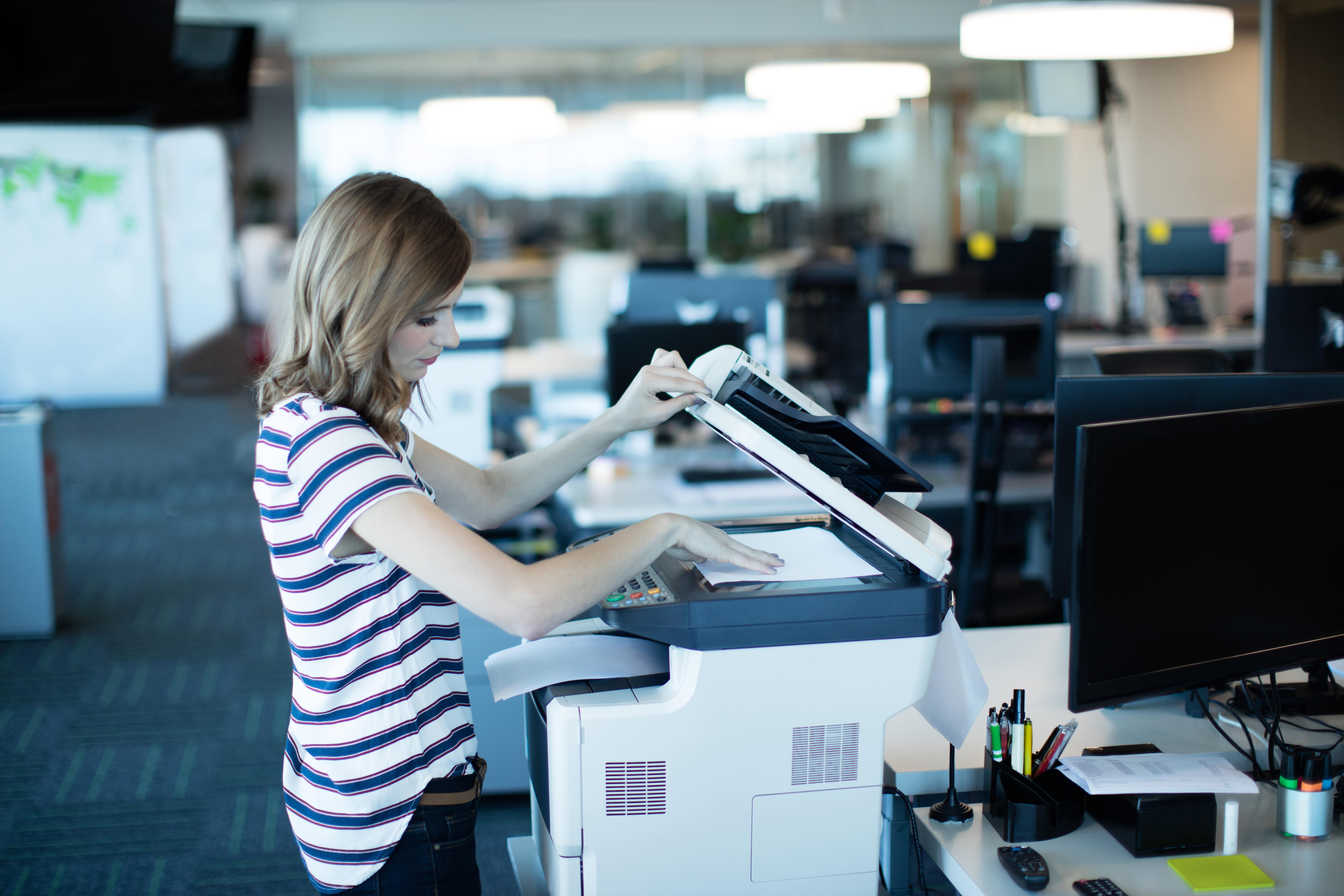 Eine junge Frau verwendet einen Kopierer der Strahlung emittieren kann